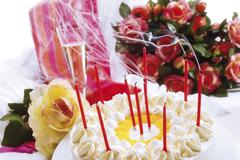 Blown-out candles on a birthday cake, bouquet of roses and a gift in the back Stock Photos