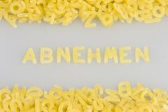 """""""abnehmen"""" (lose weight) written in noodle letters, pasta alphabet Stock Photos"""