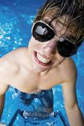 young man wearing sunglass in a swimming pool - stock photo