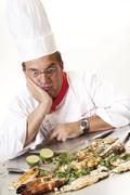 Chef looking stunned in front of a teppan grill, king prawns and grilled fish Stock Photos
