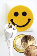 smiley face electrical outlet and euro coins: affordable electricity costs - stock photo