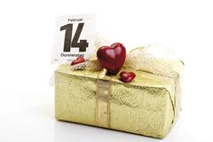 present wrapped with golden giftwrap and a bow, calendar page in background m - stock photo