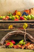autumn still life with fruit in leaves on board and vines background - stock photo