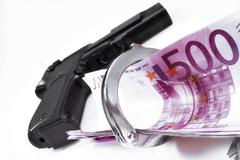 Handgun, handcuffs and cash Stock Photos