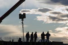 Construction workers and a crane, backlight Stock Photos