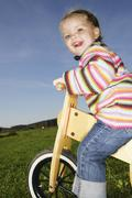 three-year-old girl riding a bicycle - stock photo