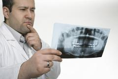 Doctor studying an x-ray image of a jaw Stock Photos