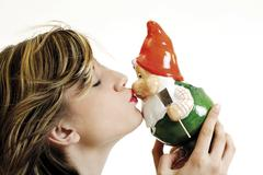 young woman kissing garden gnome - stock photo