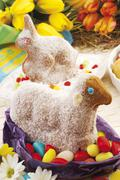 Easter bunny and lamb made of dough, sprinkled with icing sugar sitting on co Stock Photos