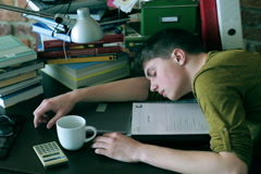 Tired student sleeping on desk and notes at home Stock Footage