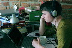 Student listening music with headphones and drinking coffee Stock Footage