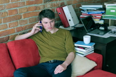 Student resting on red sofa and chatting on cellphone in the room Stock Footage