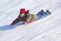 Girl sliding on her belly downhill Kuvituskuvat