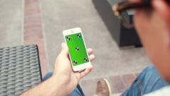 Young Man Holding Phone With Green Screen Chroma Key For Custom Content - stock footage