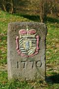 Stock Photo of historical boundary stone with colored heraldic figure and date of the year 1