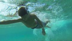 11 years old boy swims towards the Underwater camera in the sea Stock Footage