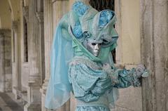 Stock Photo of turquoise mask under arcades, carneval in venice, italy