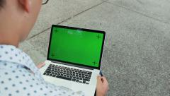 Man Typing On Laptop Computer With Blank Green Screen - stock footage