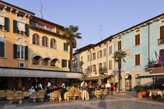 a plaza with restaurants at sunset sirmion, e lake garda, italy - stock photo