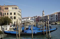 Blue covered gondolas at canale grande with rialto bridge in venice italy Stock Photos