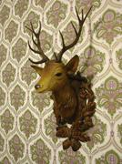 Plastic deer head on an old-fashioned wallpaper Stock Photos