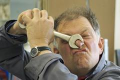 craftsman is clamping his nose with a screw wrench - stock photo