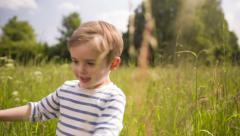 Little Boy Walking Through Tall Grass Stock Footage