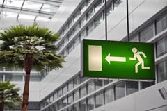Decal information for the escape route inside a building with fake palm trees Stock Photos