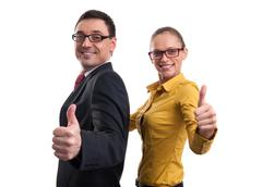 Businessman and businesswoman showing thumbs up Kuvituskuvat