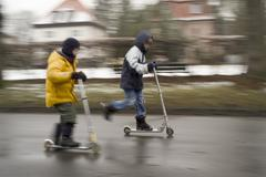 two boys on scooters in winter - stock photo