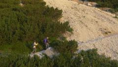 AERIAL: Young couple hiking over scree in the mountains Stock Footage