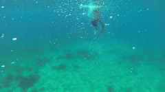 Underwater shot of 11 years old boy diving to the sea bed to catch a sea shell Stock Footage