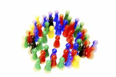 chinese checker figures are surrounding a single red token - stock photo