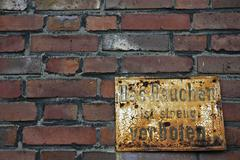 weathered prohibition sign at a clay brick wall, smoking, coking plant hansa, - stock photo