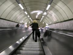 a woman steps up the escalators of a londoner subway station, london, england - stock photo
