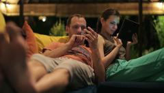Young couple looking at smartphone and tablet late at night HD Stock Footage