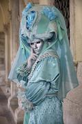 turquoise mask under arcades, carneval in venice, italy - stock photo
