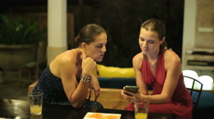 Elegant girlfriends looking at smartphone late at night HD Stock Footage