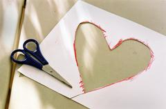 Stock Photo of of paper with shears cut out heart.