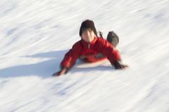 Boy sliding on his belly downhill Kuvituskuvat