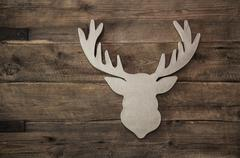 Deer head with antler for christmas decoration on wooden background. Stock Photos