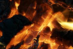smouldering wood inside the camp fire - stock photo
