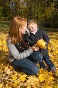 Happy family: mother with her little daughter making a walk in autumn. Stock Photos
