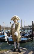 Man with traditional clothes and mask in front of gondolas at carneval in ven Stock Photos