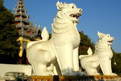Huge figures of mythological lions chinthe at the stairs to mandalay hill bur Stock Photos