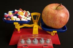 apple contra vitamine pills - stock photo