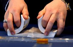 casino in berlin city. hands when mixing playing cards and sort of chips with - stock photo