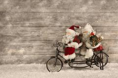 Two santa claus in hurry for buying christmas presents decorated on wooden ba Stock Photos