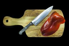 Chopping board with capsicums Stock Photos
