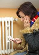 Symbolic for heating costs, woman with money freezing next to ratiator Stock Photos
